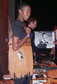 Designer, Shernett Swaby models one of her leather fringe bags.