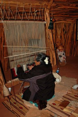 inside the hogan, a Navajo woman demonstrates rug weaving