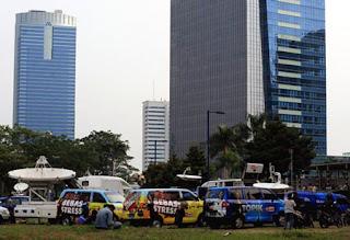 Mobil-mobil milik media terparkir di lapangan kosong di sekitar lokasi ledakan