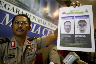 National Police spokesperson Maj. Gen. Nanan Sukarna shows police sketches of two suspected suicide bombers killed in last week's hotel bombings during a press conference in Jakarta.