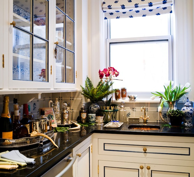 Black Countertops And Glass Front Upper Cabinets With Floral Wallpaper