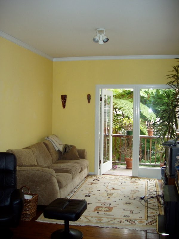 Living room before Niche Interiors' redesign with yellow walls, an Aztec rug and tan 1980s sofa
