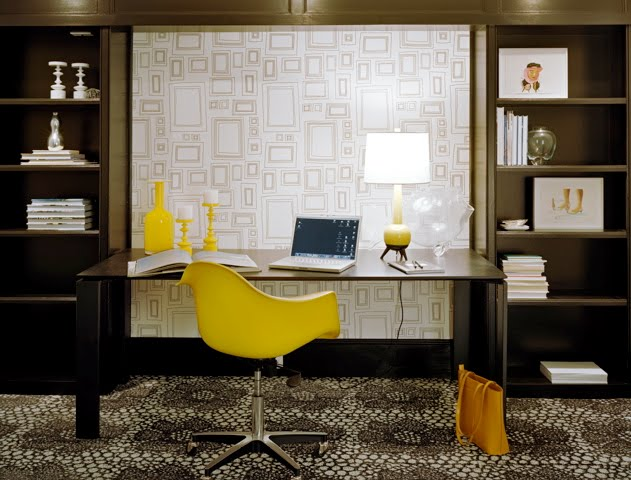Dark brown home office with built in shelves and cabinets, graphic wallpaper and a yellow Eames chair at a desk