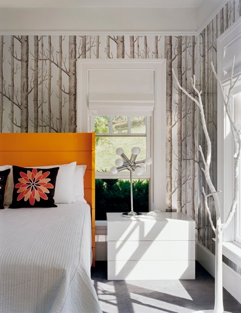 Guest bedroom by Ghislaine Vinas with branch wallpaper, orange hearboard and sleek white nightstand