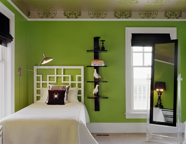Guestroom at a beach house in New York by Ghislaine Vinas with kelly green walls, white trim, green and white brocade wallpaper on the ceiling, black accessories, and a graphic white lacquer headboard
