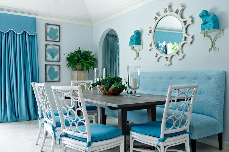 blue dining room with white lacquer rattan chairs with a circle