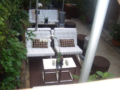 Outdoor patio with white Barcelona inspired chairs and sofa, heat lamps, orchids and metal side tables