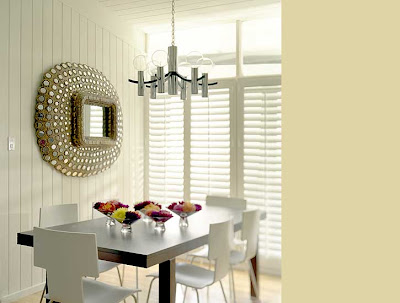 Dining room by M. Design Interiors with a glittering mirror and modern chandelier, chairs and table