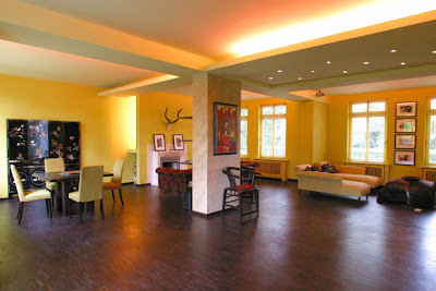 Living and dining room with yellow walls and dark wood floor