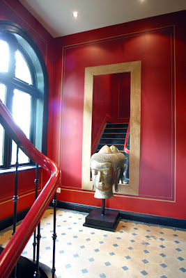 Red stairwell with tile landing, large mirror and a Buddha head
