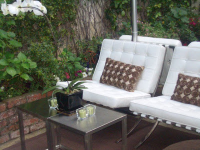 Outdoor patio with white Barcelona inspired chairs, orchids and metal side tables