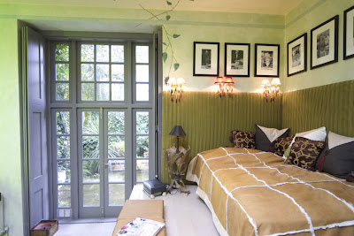 Grene bedroom in a London pied-a-terre with a lovely garden view and vine mural on the wall