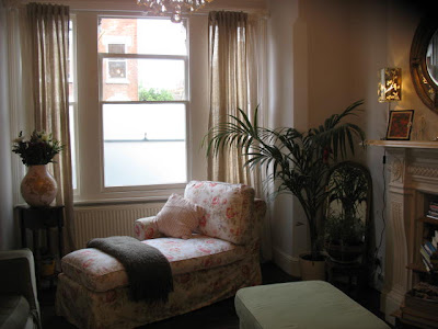 Living room in a London flat with a floral upholstered chaise lounge under a window