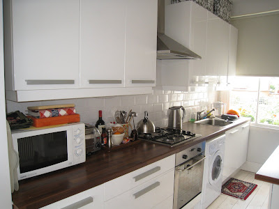 London kitchen with white tile backsplash and stainless appliances