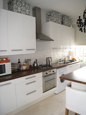 Glossy white Ikea cabinets and butcher block wood counters in a London kitchen