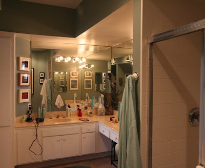 Bathroom vanity with outdated mirrors, vanity lights and cabinets prior to The Sunset Team's La Kaza Design's makeover