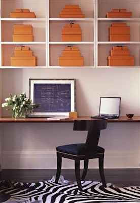Home office by Sara Story with a large wood slab wall mounted desk, zebra rug, empire style chair and Hermes orange storage boxes in white open shelves