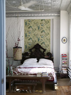 Bedroom with a pressed tin ceiling, floral wall paper, texture walls, a dark wood bench at the foot of the bed and a black carved headboard