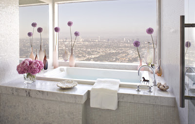 Marble bathroom by Jeff Andrews with a picture window with a view of Los Angeles