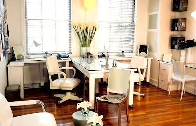 White home office by Jeff Andrews with white glass top desk, classic metal office chairs on wheels, white lower file cabinets with a Philippe Starck Hudson accent chair