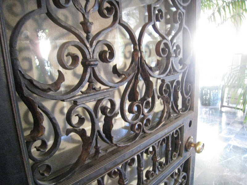 Large wrought iron scroll double doors leading to the grand entrance hall at the Greystone Mansion
