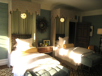 Guest bedroom in the Greystone Mansion with twin canopy beds draping being the head boards and yellow bolster cushions