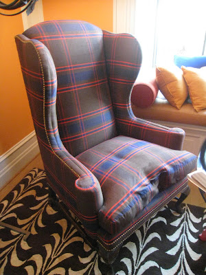 Plaid armchair on a bold patterned rug in a bedroom by James Lumsden in the Greystone Mansion