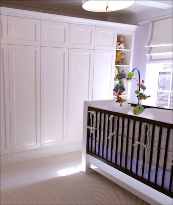 Doors to a built in closet in a New York nursery by Area Interior Design