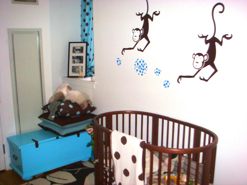 Nursery with dark brown walnut stained wood Stokke Sleepi Crib from tottini, a turquoise trunk, blue and brown polka dot curtains and two monkey decals on the wall