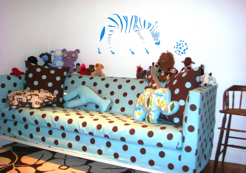Blue and brown polka dot Jonathan Adler Lampert Sofa covered in toys in a nursery with a blue zebra playing with a ball decal