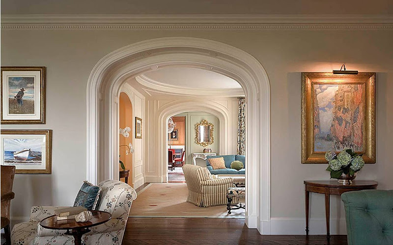 Succession of bright, white painted arched entryways with molding and paneling in a New York Apartment designed by Katie Leede