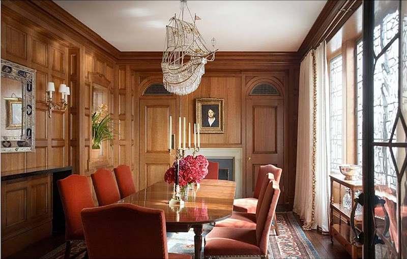 Traditional dining room by Katie Leede with wood paneling, a crystal ship chandelier over an oval table and rust colored velvet chairs