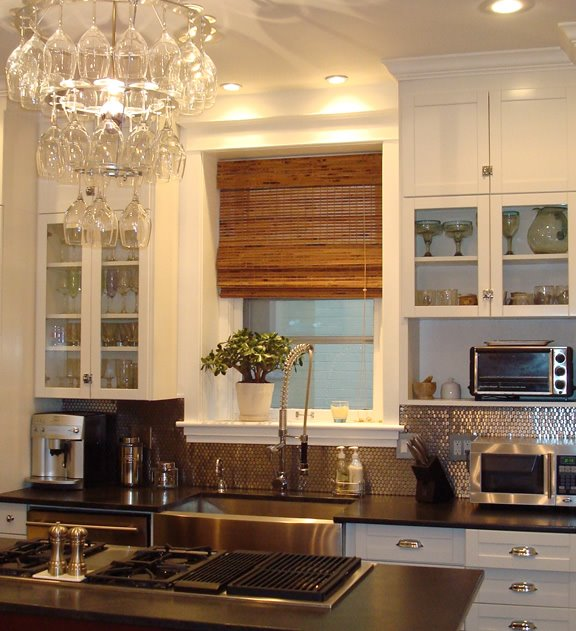 Kitchen with Mod Walls' penny round stainless steel mosaic tile backsplash, stainless steel farmhouse sink, wine glass chandelier and white upper cabinets with glass fronts
