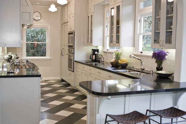 Kitchen by Tom Newman with black, white and grey terrazzo tile plaid floor, white cabinets and drawers, black counter tops and stainless appliances