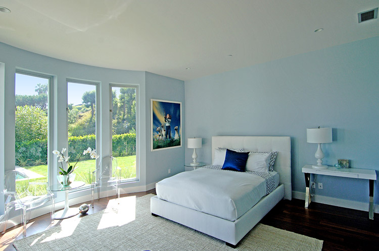 wall white upholstered bed white table lamps and light blue walls