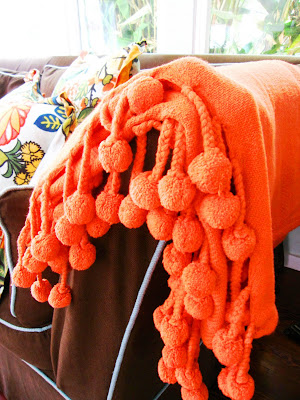 Bright orange throw with pompoms from Calyspo Home on a brown sofa with turquoise piping