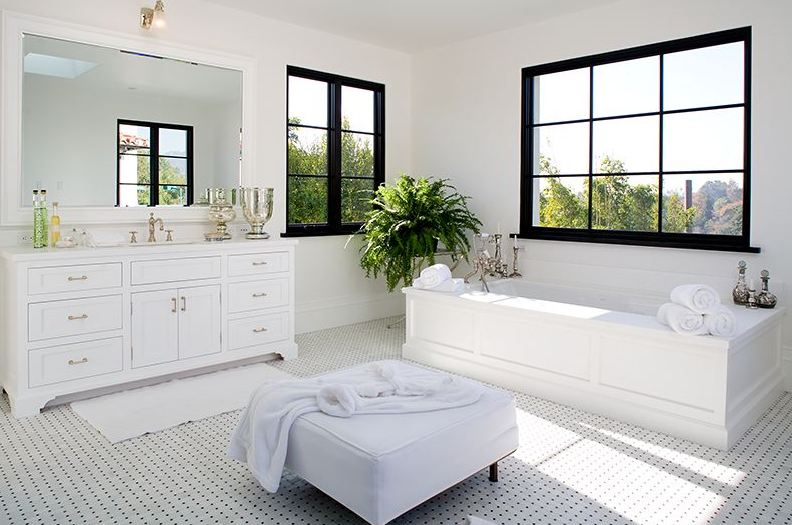 Black and white Master bathroom in a Spanish revival home with white freestanding tub and black paned windows