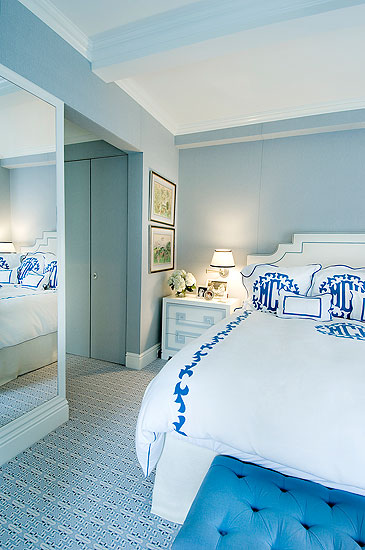 Master bedroom with crisp white monogrammed linens, a majestic white headboard and clean white furniture