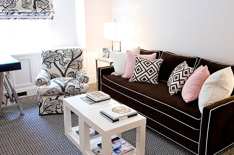 Living room designed by Christina Murphy with brown sofa with white piping and a black and white graphic armchair