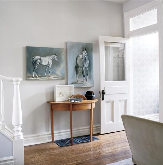 Foyer in a cottage with blue-grey paintings of horses