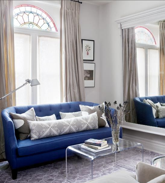 Bright blue sofa and a stainglass window in a Victorian cottage