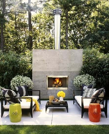 Outdoor patio with black furniture, green and orange garden stools,a fireplace and lots of planets
