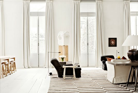 rustic white living room with brown and white rug with a drop step
