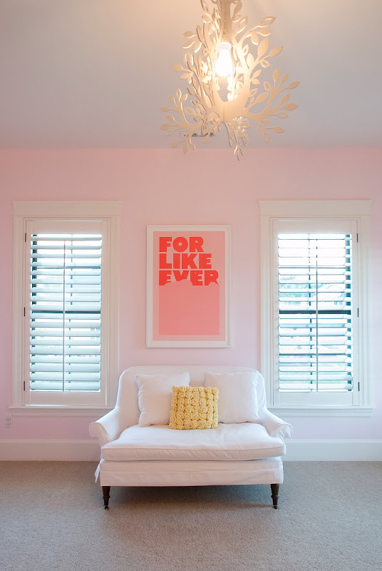 Nursery with pale pink walls, simple art, a white love seat, and modern tole chandelier