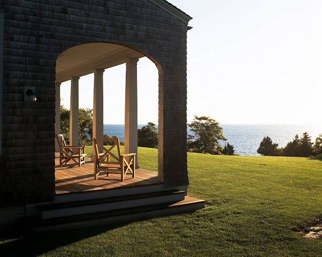 Covered outdoor patio by Peter Pennoyer with columns and an arched entryway and a view of a large body of water