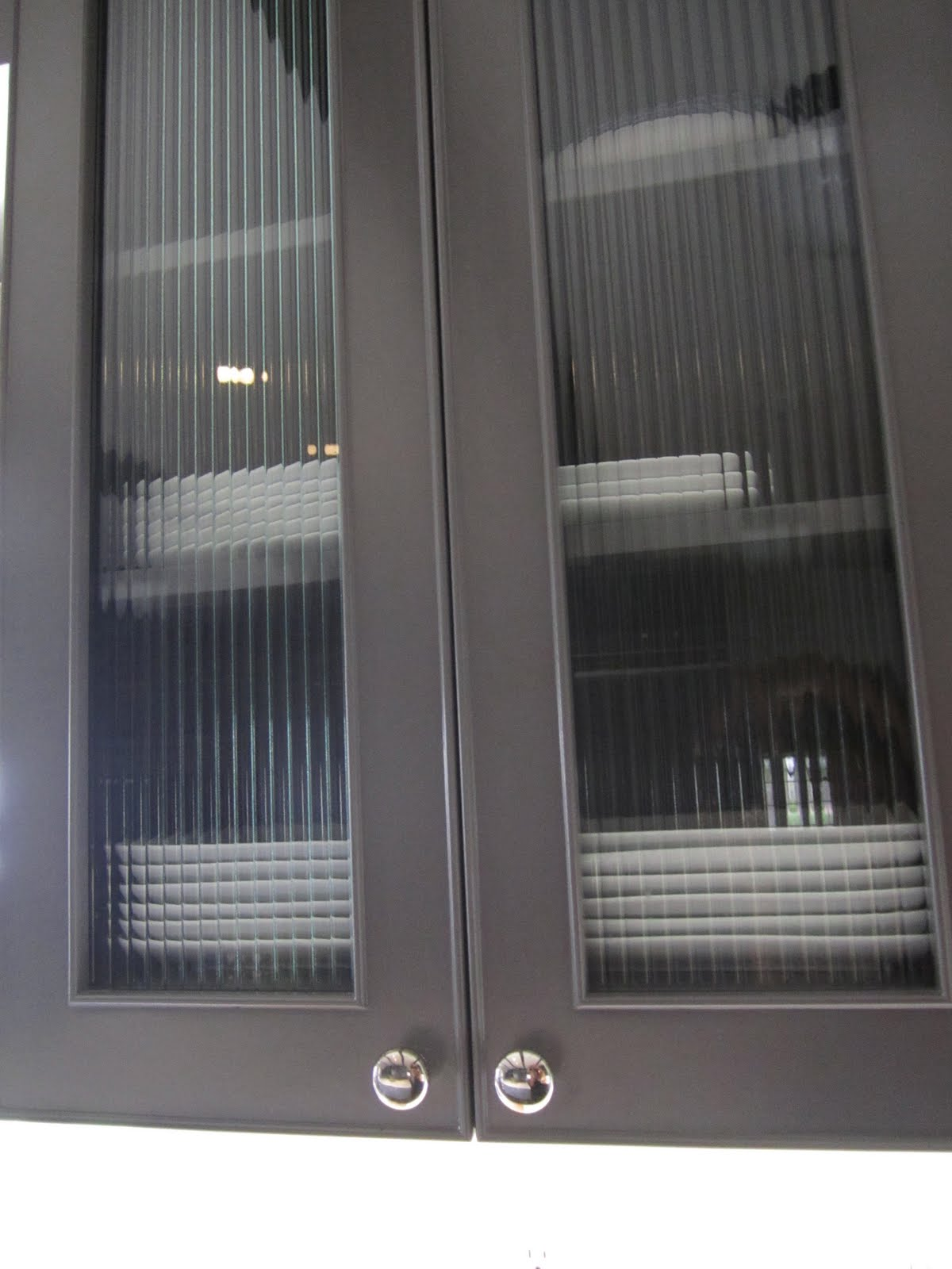 Grey cabinet with reeded glass upper cabinet doors in a kitchen
