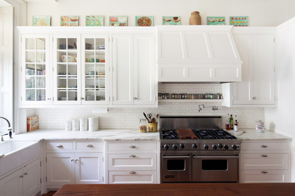 Kitchen with high ceilings, white wood paneled cabinets and drawers, a subway tile backsplash, marble counters, stainless appliances, and a butcher block topped island