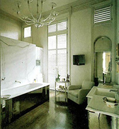 Bathroom with white chandelier, black tub, wood floor, white armchair, large windows and mirrored cabinets beneath the sink