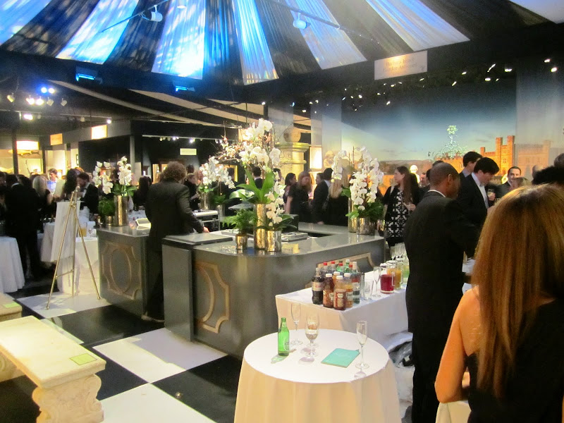 People mingling under a tent at the Young Collector's Night at the Winter Antiques Show