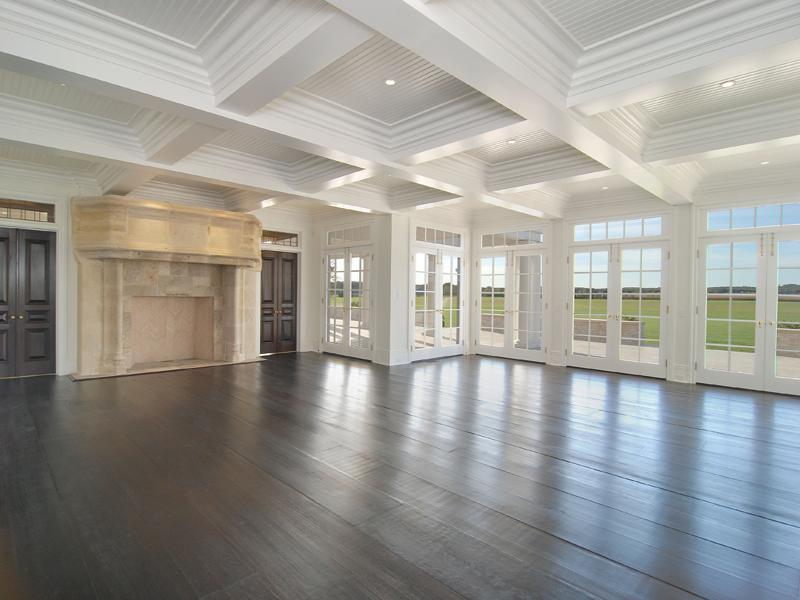 Empty living or family room in a Hamptons farm with coffered ceiling, large windows, French doors, wood floor and a massive fireplace